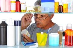 Uomo invecchiato centrale davanti all'armadietto di medicina Immagini Stock