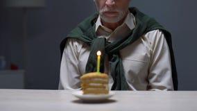 Uomo invecchiato che si siede da solo con la torta di compleanno, abbandonata dai parenti, problemi stock footage