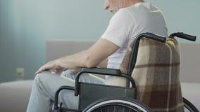Uomo invecchiato che si siede in sedia a rotelle che esamina le gambe e che annuisce col capo, capacità persa di camminare stock footage