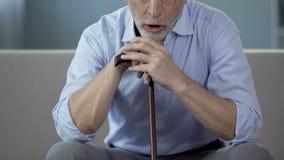 Uomo invecchiato che si siede sul sofà e che tossisce, complicazioni di polmonite, salute video d archivio