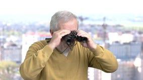 Uomo invecchiato con il binocolo video d archivio
