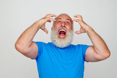Uomo invecchiato con la barba bianca che posa alla macchina fotografica che esprime rabbia Immagine Stock