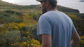 Uomo invecchiato medio felice che sorride, camminando intorno alla bella linea costiera dell'oceano del Big Sur coperta di fiori  video d archivio
