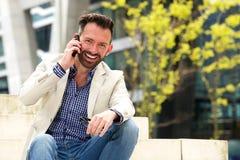 Uomo invecchiato mezzo allegro che parla sul telefono cellulare Immagini Stock