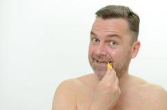 Uomo invecchiato mezzo che usando spazzola interdental Immagini Stock Libere da Diritti