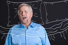Uomo invecchiato piacevole che dorme nel suo letto immagini stock
