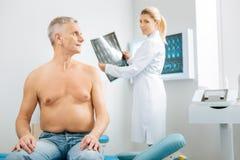 Uomo invecchiato piacevole che si gira verso il suo medico fotografie stock