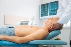 Uomo invecchiato serio che si trova sul letto medico immagini stock libere da diritti