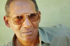 Uomo invecchiato serio con gli occhiali da sole che esaminano macchina fotografica Fotografia Stock Libera da Diritti