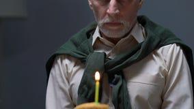 Uomo invecchiato turbato che si siede da solo con la torta di compleanno sulla tavola, abbandonata dalla famiglia video d archivio
