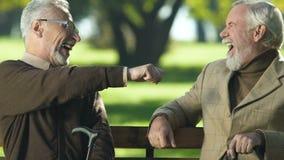 Uomo invecchiato umoristico che scherza con l'amico in parco, pizzicante naso, positività di vecchiaia video d archivio