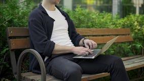Uomo irriconoscibile che scrive sul computer portatile che si siede sul banco video d archivio