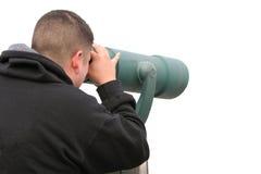 Uomo isolato che osserva il binocolo di throu Immagini Stock