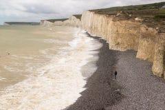 Uomo isolato che sta da solo su una spiaggia della ghiaia sotto le scogliere bianche Fotografia Stock Libera da Diritti