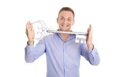 Uomo isolato fiero di affari che tiene una chiave per una nuova casa nel suo Immagini Stock Libere da Diritti