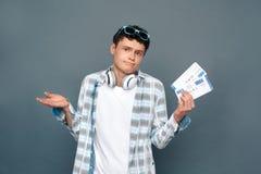 Uomo isolato sulla condizione grigia di concetto di turismo della parete che tiene un dubbio di due biglietti fotografia stock libera da diritti
