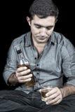 Uomo ispanico ubriaco e depresso con un fondo nero Fotografia Stock