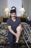 Uomo ispano che allunga ginocchio bendato fotografia stock