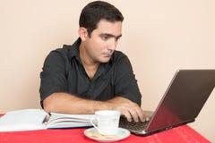 Uomo ispano che studia o che fa il lavoro d'ufficio a casa Fotografie Stock Libere da Diritti