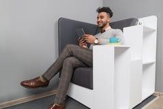 Uomo ispano di affari che per mezzo dello Smart Phone Sit Modern Office Cafe Businessman delle cellule Immagini Stock