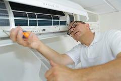 Uomo ispano di riparazione del condizionamento d'aria che esegue manutenzione fotografie stock libere da diritti