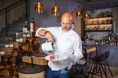 Uomo italiano bello calvo con una barba in cuoco unico uniforme bianco in un ristorante che posa con un sorriso a trentadue denti fotografie stock libere da diritti