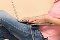 Uomo in jeans con un computer portatile Immagine Stock