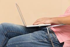 Uomo in jeans con un computer portatile Immagini Stock