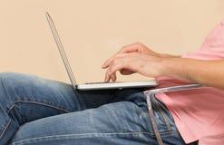 Uomo in jeans con un computer portatile Immagine Stock Libera da Diritti
