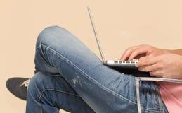Uomo in jeans con un computer portatile Fotografie Stock Libere da Diritti