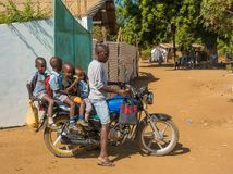 Uomo keniano con quattro bambini sulla motocicletta Immagine Stock
