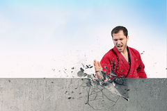 Uomo in kimono che tagliato parete Fotografia Stock Libera da Diritti