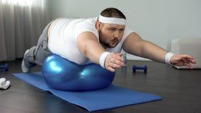 Uomo laborioso obeso che pratica esercizio statico, programma di formazione di forza fotografia stock libera da diritti