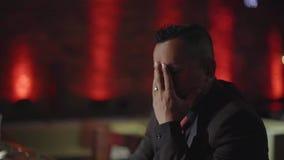 Uomo latino alla moda che si siede da solo al contatore della barra con un whiskey stock footage