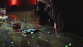 Uomo latino alla moda che si siede da solo al contatore della barra con un whiskey archivi video