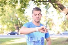Uomo latino che esamina il suo orologio Immagine Stock