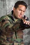 Uomo latino militar del soldato che indica una pistola Fotografie Stock