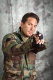 Uomo latino militar del soldato che indica una pistola Immagine Stock