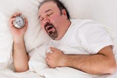 Uomo letargico che sbadiglia come lotta per svegliare Fotografia Stock
