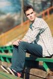 Uomo libero dei pantaloni a vita bassa che si siede su un banco nella città Fotografia Stock