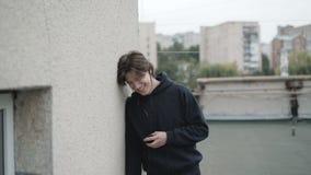Uomo libero facendo uso dello smartphone e delle cuffie e dell'esultanza all'aperto video d archivio