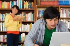 Uomo in libreria con il computer portatile Fotografia Stock