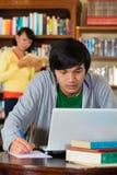 Uomo in libreria con il computer portatile Immagini Stock
