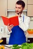 Uomo in libro di cucina blu della lettura del grembiule Fotografia Stock Libera da Diritti