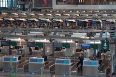 Uomo: lo scrittorio di controlla l'aeroporto di Malpensa Fotografia Stock Libera da Diritti