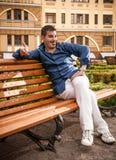 Uomo macho che si siede sul banco Fotografia Stock Libera da Diritti