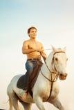 Uomo macho e cavallo sui precedenti del cielo e dell'acqua Modo del ragazzo immagine stock libera da diritti