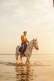 Uomo macho e cavallo sui precedenti del cielo e dell'acqua Modo del ragazzo fotografie stock