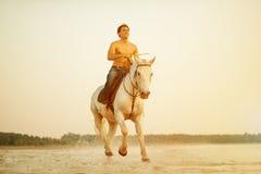 Uomo macho e cavallo sui precedenti del cielo e dell'acqua Modo del ragazzo fotografia stock