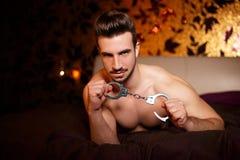 Uomo macho sexy con le manette che mette su letto Immagine Stock Libera da Diritti